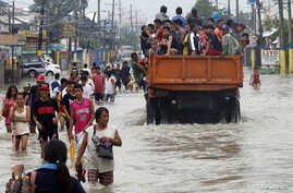 Flood victims are evacuated on a truck while other residents wade through floodwaters on a street in Bacoor near Manila, Philippines, August 20, 2013.