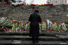 "FILE - A woman mourns before a memorial to those killed in violence in Kiev, Feb. 25, 2014 — the day that Ukraine's parliament voted to send fugitive President Viktor Yanukovich to be tried by the International Criminal Court for ""serious crimes"" com"