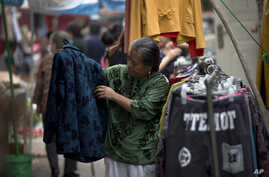 A woman checks a jacket for sale at an open market along a Hutong alley in Beijing, China, September 9, 2012.