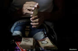 A man counts his money to place horse racing bets at a small warehouse on the outskirts of Caracas, Venezuela, October 7, 2017.