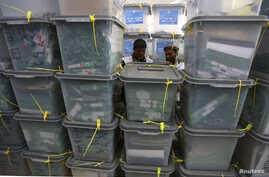 FILE - Afghan electoral workers sort ballot boxes at a counting centre in Kabul.