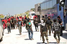 """Fighters from a coalition of rebel groups called """"Army of Fatah"""" and members of the Syrian Arab Red Crescent stand near buses and ambulances on the outskirts of Idlib city,  preparing to enter the two besieged Shi'ite towns of al-Foua and Kefraya to"""