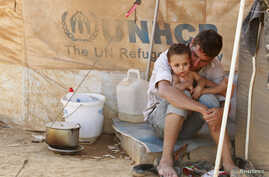 A Syrian refugee holds his child as he sits by his tent at Al Zaatri refugee camp in the Jordanian city of Mafraq, near the border with Syria September 9, 2012.