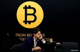 FILE - A man works on a laptop beneath the Bitcoin logo at the Consensus 2018 blockchain technology conference in New York City, May 16, 2018.