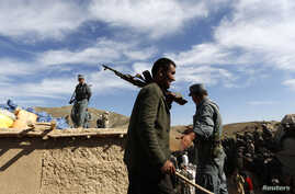 Afghan policemen watch as displaced villagers wait for aid near the site of a landslide at the Argo district in Badakhshan province, Afghanistan, May 6, 2014.