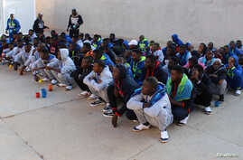 FILE - Migrants wait before being deported by Libyan authorities, in Misrata, Libya, Feb. 19, 2018.