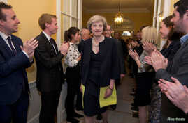Staff applaud as Britain's new Prime Minister Theresa May, and her husband Philip, walk into 10 Downing Street after May had met Queen Elizabeth in Buckingham Palace, in central London, Britain, July 13, 2016.