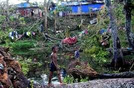 Children play in water amongst the debris of fallen trees just outside Vanuatu's capital, Port Vila, after Cyclone Pam ripped through the island nation, March 17, 2015..