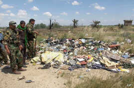 In this image made from video, Iraqi Shi'ite militiamen stand near a mass grave, believed to contain the bodies of Iraqi soldiers killed by Islamic State group militants when they overran Camp Speicher military base last June, in Tikrit, Iraq, April