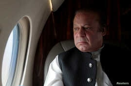 FILE - Pakistani Prime Minister Nawaz Sharif looks out the window of his plane after attending a ceremony to inaugurate the M9 motorway between Karachi and Hyderabad, Pakistan.