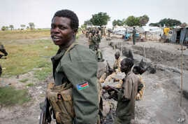 FILE - South Sudanese government soldiers stand in trenches in Malakal, South Sudan.