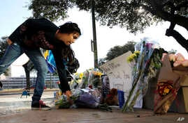 Faith Reyna leaves flowers at a make-shift memorial for slain San Antonio police officer Benjamin Marconi, 50, a 20-year veteran of the force, Monday, Nov. 21, 2016. Marconi was fatally shot during a traffic stop near police headquarters. Nov. 20, 2