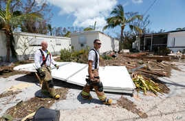 FILE - Members of the Monroe County Fire Rescue check on residents at the Driftwood Trailer Park, Sept. 12, 2017, in Tavernier, Fla., in the Florida Keys.