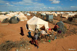 Refugees stand outside their tent at the Ifo Extension refugee camp in Dadaab, near the Kenya-Somalia border, Oct. 19, 2011. Ahmed Warsame, the new UNHCR director for global emergencies has led UNHCR operations in Dadaab.