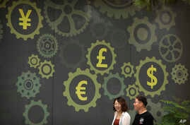 People walk past a mural on a bank showing symbols for American, Chinese and other world currencies in Beijing, July 7, 2018.