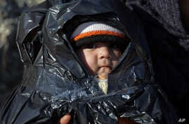 A child is covered in plastic as migrants travel by dinghy to the Greek island of Chios, from the Turkish coast near Cesme, Izmir, Turkey, Nov. 4, 2015. More than 300,000 people have traveled on dinghies and boats from nearby Turkey to Greek islands