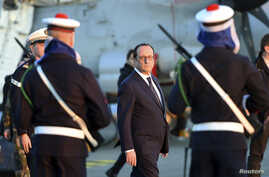 French President Francois Hollande reviews troops during his visit aboard the French aircraft carrier Charles de Gaulle January 14, 2015, off the coast of Toulon, southern France.