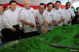 Malaysia's Prime Minister Najib Razak and Transport Minister Liow Tiong Lai look at a model of the East Coast Rail Line at Kuantan Bahang, Malaysia, Aug. 9, 2017.