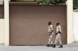 Soldiers walk in front of the headquarters of Constitutional Council before the proclamation of the final list of candidates for the presidential election in Abidjan, Sept. 9, 2015.