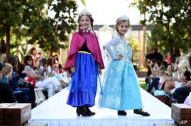 """FILE - Child models are seen dressed up as Anna (L) and Elsa (R) from Disney's """"Frozen"""" at a Halloween fashion show."""