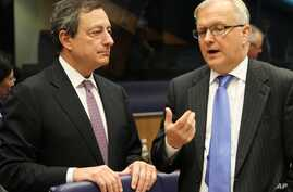 President of the European Central Bank Mario Draghi, left, looks on as he listens to European Commissioner for Economic and Monetary Affairs Olli Rehn, during the Eurogroup meeting, in Luxembourg, October 8, 2012.