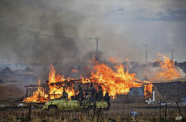 A machinegun-mounted truck manned by members of the Sudan Armed Forces (SAF) drive past burning businesses and homesteads in the center of Abyei, central Sudan in this handout photograph released by United Nations Mission in Sudan on May 28, 2011