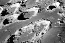 FILE - This Dec. 29, 1968, photo made available by NASA shows the large moon crater Goclenius, foreground, approximately 40 statute miles in diameter, and three clustered craters Magelhaens, Magelhaens A, and Colombo A, during the Apollo 8 mission. F