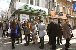 FILE - People are seen lining up to withdraw money at an ATM at a Privatbank branch in Simferopol, Crimea, March 14, 2014.