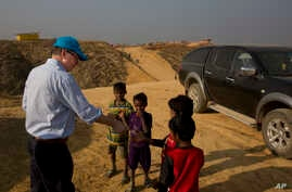 UNICEF Deputy Executive Director Justin Forsyth, left, shares biscuits with Rohingya refugee children as he leaves Balukhali refugee camp 50 kilometres (32 miles) from, Cox's Bazar, Bangladesh Wednesday, Jan. 24, 2018.