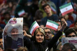 A pro-reform Iranian woman who supports President Hassan Rouhani for the May 19 presidential election holds his picture, on special edition of Shargh daily, and Iranian flag in a campaign rally in Tehran, Iran,  April, 29, 2017.