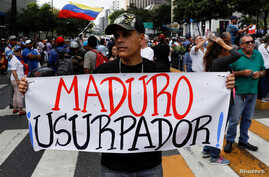 """A man holding a placard that reads """"Maduro usurper"""" takes part in a gathering with members of the Venezuelan National Assembly in Caracas, Venezuela, Jan. 11, 2019."""