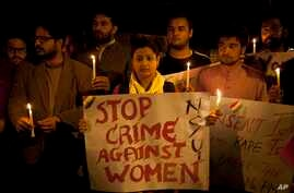 FILE - Indian youth hold candles during a protest against sexual violence in New Delhi.