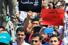 """Lebanese protesters hold Arabic placards that read: """"#Aleppo,"""" at left, and """"Sorry, Aleppo, you are not Paris,"""" at right, during a protest to show solidarity with Aleppo, in Sidon, Lebanon, May 6, 2016. Russian and Syrian officials denied Friday that"""