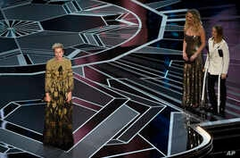"Frances McDormand accepts the award for best performance by an actress in a leading role for ""Three Billboards Outside Ebbing, Missouri"" as Jennifer Lawrence and Jodie Foster look on from right at the Oscars, March 4, 2018."
