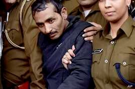 Shiv Kumar Yadav, 32, center, a driver from the international taxi-booking service Uber, is surrounded by police as he is brought out after being produced in a court in New Delhi, India, Dec. 8, 2014.