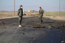 In this undated photo made avaialble March 14, 2015, by the Kurdistan Region Security Council, Kurdish soldiers survey what Kurds now say was the site of a chemical-weapons bombing between Mosul, Iraq, and the Syrian border in northern Iraq.