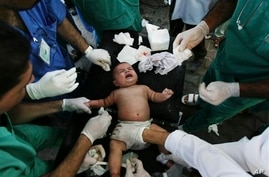 Palestinian medics treat baby wounded in missile strike in Rafah, southern Gaza Strip, Aug. 4, 2014.