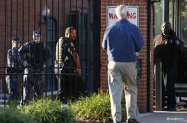 A Navy Yard personnel approaches a security checkpoint as he returns to work two days after a gunman killed 12 people before police shot him dead, in Washington, Sept. 18, 2013.