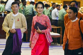 FILE -  Myanmar opposition leader Aung San Suu Kyi, center, walks along with other lawmakers of her National League for Democracy party as they leave after a regular session of the lower house of parliament in Naypyitaw, Myanmar.