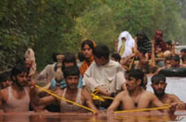 Local residents evacuate to safety in a flood-hit area of Nowshera, Pakistan, 30 Jul 2010
