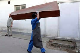 FILE - An Afghan man carries an empty casket in Kabul, Afghanistan, Sunday, July 15, 2018. Afghanistan has faced intense attacks by both the Taliban and the country's Islamic State affiliate recently.