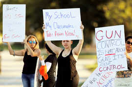 Angelina Lazo, center, an 18-year-old senior at Marjory Stoneman Douglas High School, who said she lost two friends in the shooting at her school two days ago, joins other gun control proponents with placards at a street corner in Coral Springs, Flor
