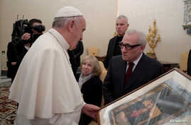Pope Francis receives a gift from film director Martin Scorsese (right) during a private audience at the Vatican Nov. 30, 2016.