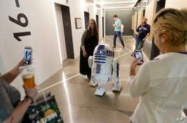 FILE - A life-size R2-D2 droid from the 'Star Wars' movie franchise mingles with workers at an Amazon.com building, May 4, 2017, in Seattle.