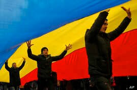 FILE - People walk under a huge Moldovan national flag, in Chisinau, Moldova, Nov. 14, 2016.