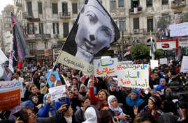 Women wave a flag showing pharaoh Queen Hatshepsut, the only woman that ruled Egypt, and anti-Muslim Brotherhood banners during a demonstration to mark International Women's Day, Cairo, Egypt, March 8, 2013.