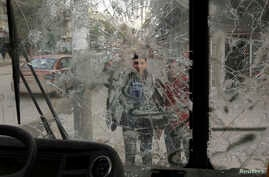 Boys are pictured through a broken windshield as they stand on a street in Aleppo, Feb. 28, 2013.