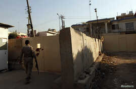 FILE - A security guard walks outside the Al-Jazeera building in Baghdad April 28, 2013. Iraq's media commission on Thursday ordered the Qatar-based broadcaster's Baghdad bureau closed for one year, citing 'continuing violations' of rules regulating