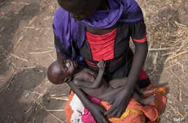 Adel Bol, 20, cradles as she her 10-month-old daughter Akir Mayen at a food distribution site in Malualkuel in the Northern Bahr el Ghazal region of South Sudan.