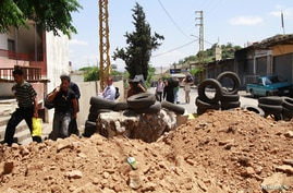 People carry their belongings as they try to make their way across a road blocked by relatives and residents in Lebanon's northern border town of Abboudiyyeh, in Akkar province, to protest the kidnapping of Lebanese farmers unidentified gunmen who to